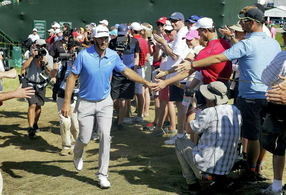 Dustin Johnson greets fans on the way to the 14th tee during the second round of the U.S. Open on Friday. Photo: John Minchillo — The Associated Press  / AP