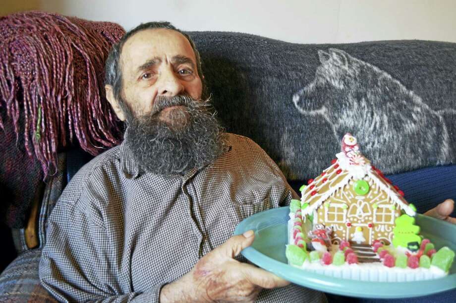 John Lomartra shows off his gingerbread house. Photo: Cassandra Day — The Middletown Press