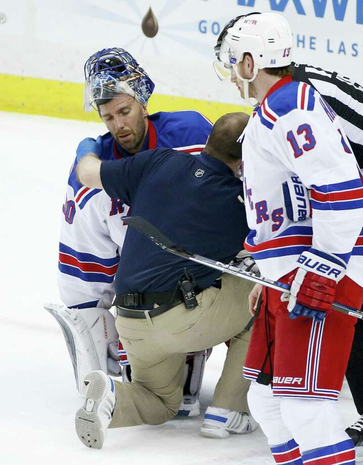 Rangers goalie Henrik Lundqvist (30) is helped by a trainer after getting a stick to the face during the first period on Wednesday. Photo: The Associated Press File Photo  / Copyright 2016 The Associated Press. All rights reserved. This material may not be published, broadcast, rewritten or redistributed without permission.
