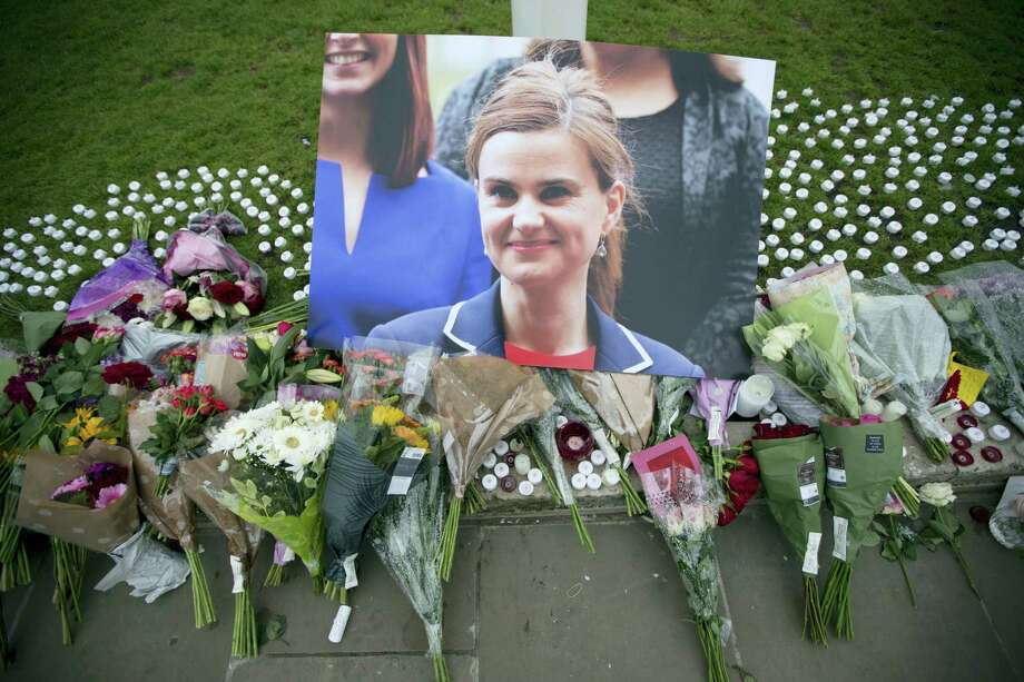 An image and floral tributes for Jo Cox, lay  on Parliament Square, outside the House of Parliament in London, Friday, June 17, 2016, after the 41-year-old British Member of Parliament was fatally injured Thursday in northern England. The mother of two young children was shot to death Thursday afternoon in her constituency near Leeds. A 52-year-old man has been arrested but has not been charged. He has been named locally as Tommy Mair. Photo: AP Photo — Matt Dunham / Copyright 2016 The Associated Press. All rights reserved. This material may not be published, broadcast, rewritten or redistribu