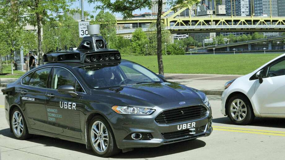 A Ford Fusion hybrid outfitted with radars, laser scanners and high-resolution cameras drives along the streets of Pittsburgh. Uber said Thursday, Aug. 18, 2016, that passengers in Pittsburgh will be able to summon rides in self-driving cars with the touch of a smartphone button in the next several weeks. The high-tech ride-hailing company said that an unspecified number of autonomous Ford Fusions with human backup drivers will pick up passengers just like normal Uber vehicles. Riders will be able to opt in if they want a self-driving car, and rides will be free to those willing to do it, spokesman Matt Kallman said. Photo: Uber Via AP, File / Uber
