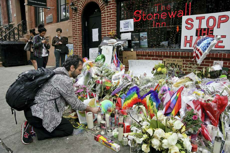A man lights candles on a memorial outside the Stonewall Inn for victims of the Orlando shooting Thursday in New York. Photo: ASSOCIATED PRESS  / Copyright 2016 The Associated Press. All rights reserved. This material may not be published, broadcast, rewritten or redistribu