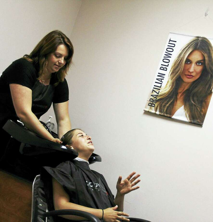 Stylist Danielle Timbro rinses a customer's hair at Micheli's Unisex Salon in Middlefield. Photo: Kathleen Schassler — The Middletown Press  / Kathleen Schassler All Rights