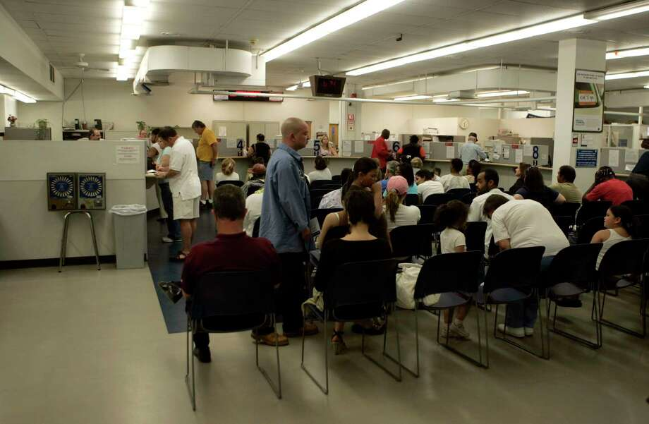 In this May 21, 2009 file photo, people wait to transact business at the Wethersfield office of the state Department of Motor Vehicles. Photo: AP Photo — Bob Child, File / AP