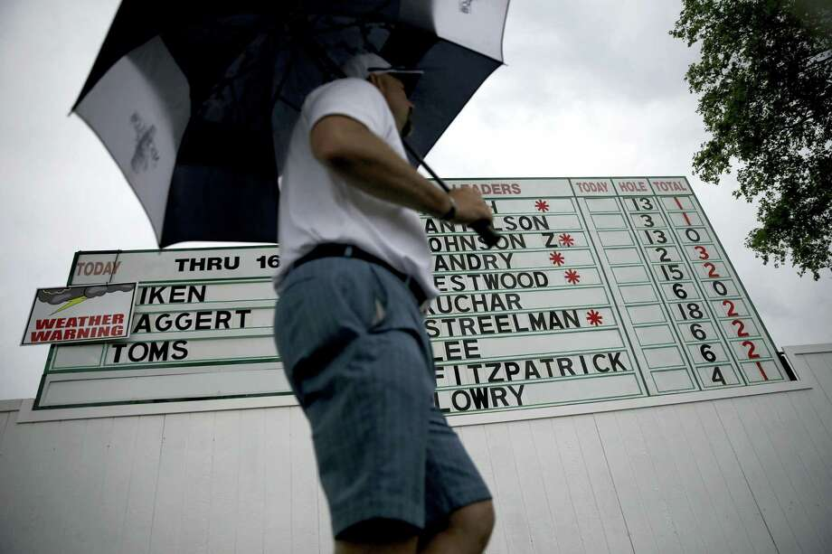 A fan with an umbrella walks past the leaderboard during a rain delay during the first round of the U.S. Open on Thursday. Photo: John Minchillo — The Associated Press  / AP