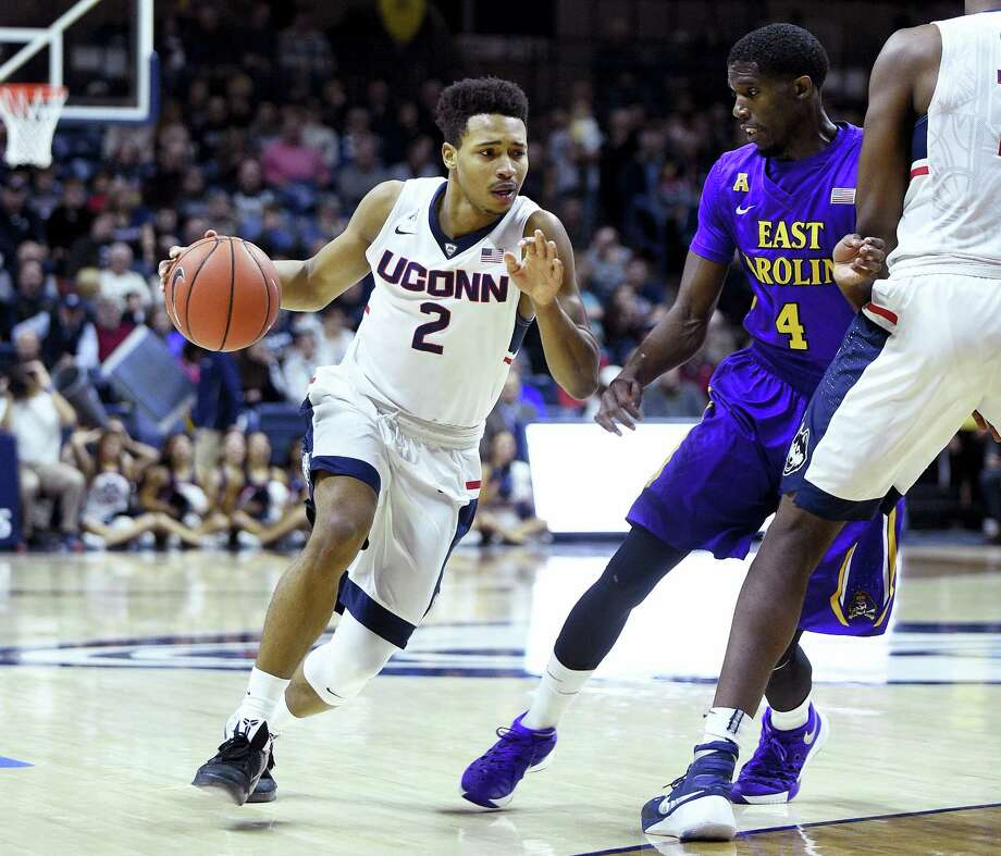 Connecticut's Jalen Adams (2) drives past East Carolina's Prince Williams (4) during the first half of an NCAA college basketball game in Storrs, Conn., on Sunday, Feb. 7, 2016. (AP Photo/Fred Beckham) Photo: AP / FR153656 AP