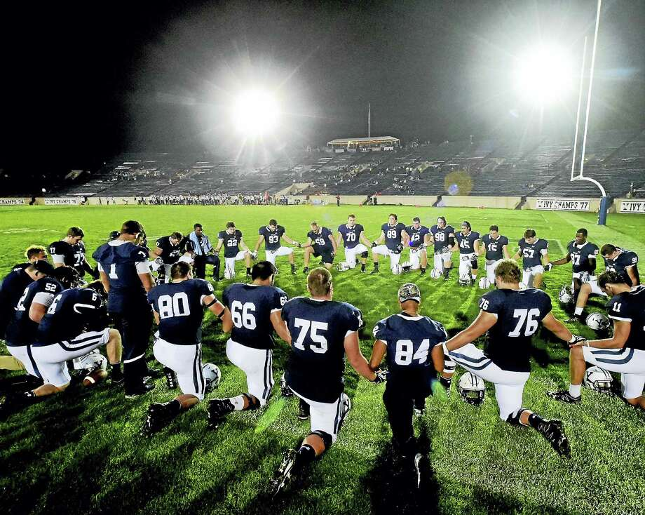 Members of the Yale football kneel for prayer before the first night football game at Yale Bowl on Friday. Photo: Peter Hvizdak — Register  / ©2016 Peter Hvizdak