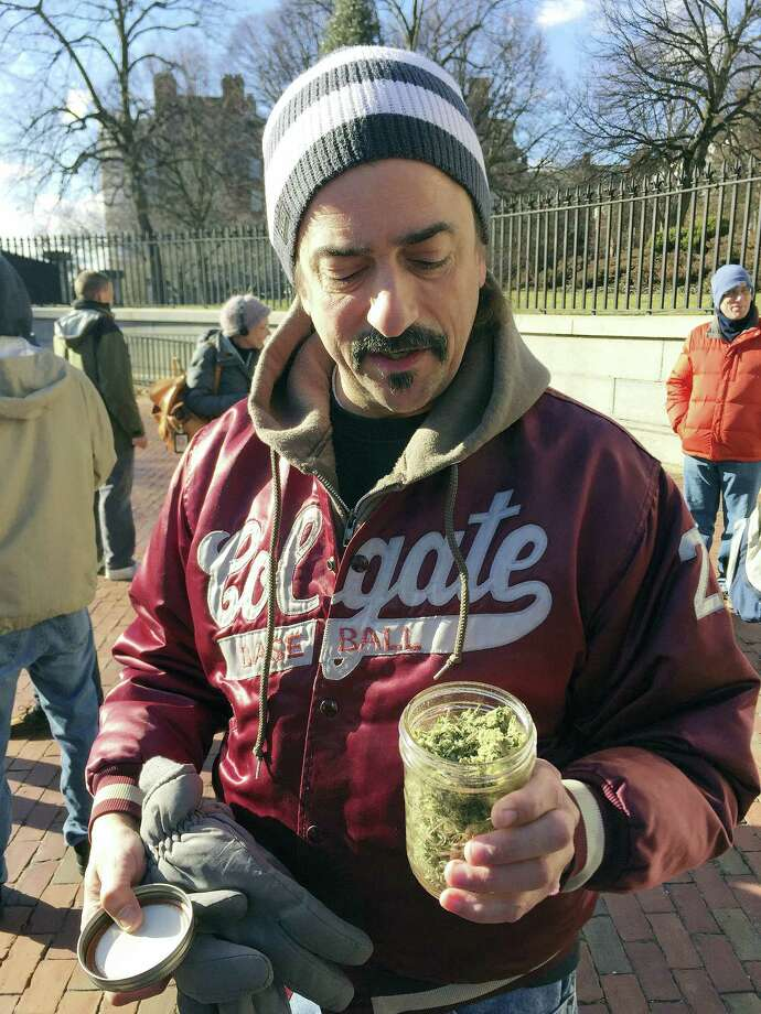 Keith Saunders, a marijuana activist from Scituate, Mass., holds a jar that he says contains just under an ounce of pot, now legal in Massachusetts. Advocates gathered in front of the Massachusetts Statehouse Thursday to celebrate the voter-approved law legalizing the recreational use of marijuana that took effect at midnight Thursday. Photo: Bob Salsberg — AP Photo / Copyright 2016 The Associated Press. All rights reserved.