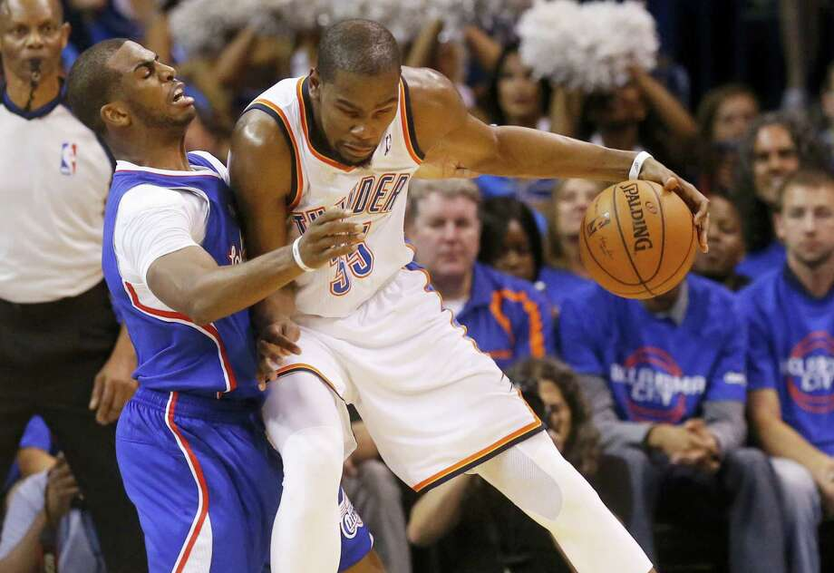 Oklahoma City Thunder forward Kevin Durant, right, drives against Los Angeles Clippers guard Chris Paul, left, in the second quarter of Game 1 of the Western Conference semifinal NBA basketball playoff series in Oklahoma City on May 5, 2014. Photo: AP Photo/Sue Ogrocki  / AP