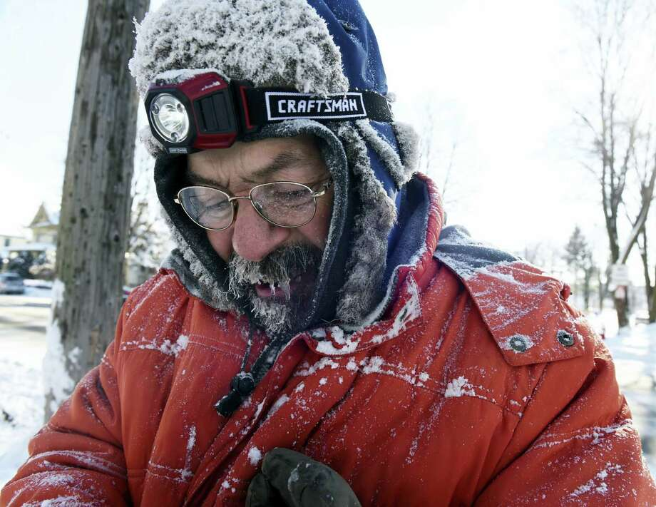 In this Monday photo, ice forms in Carl Bentson's beard and mustache as he clears sidewalks near Colborne Street and St. Clair Avenue in St. Paul, Minn. Temperatures dipped below zero for the first time this winter and will hover near there for most of the week. Photo: Scott Takushi — Pioneer Press Via AP  / Pioneer Press