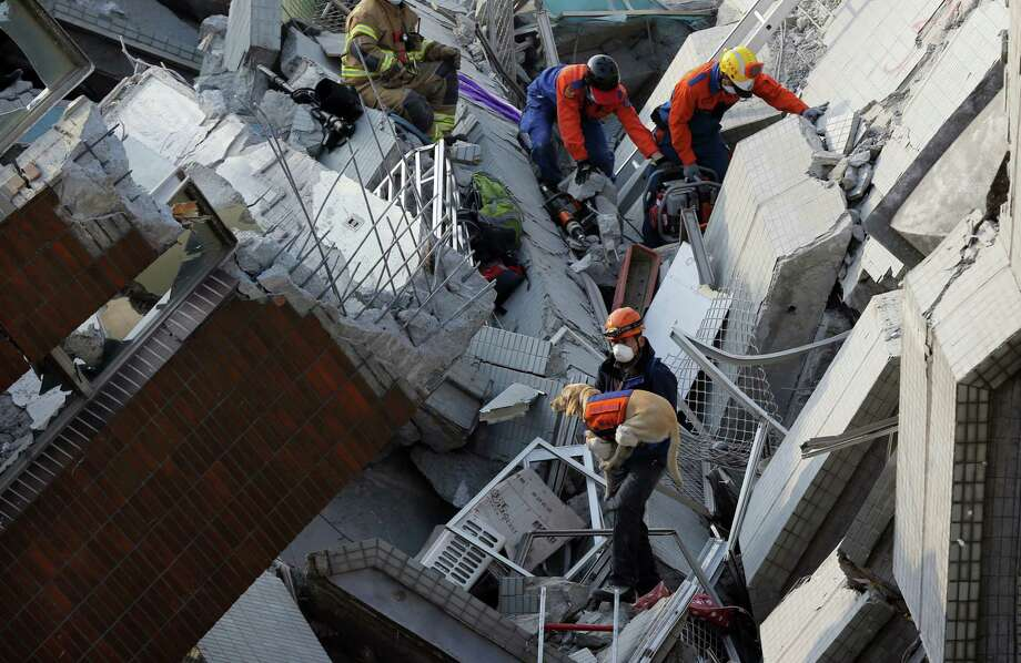 A canine rescue team searches for the missing in a collapsed building, after an early morning earthquake in Tainan, Taiwan, Saturday, Feb. 6, 2016. A powerful, shallow earthquake struck southern Taiwan before dawn Saturday. (AP Photo/Wally Santana) Photo: AP Photo/Wally Santana  / AP
