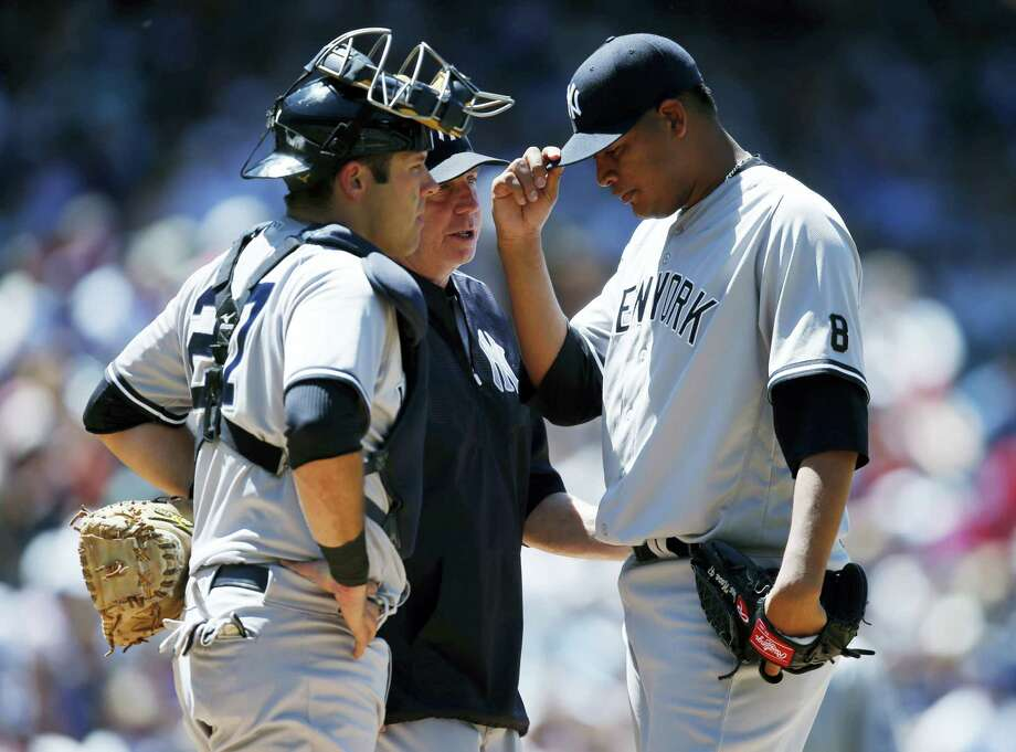 New York Yankees starting pitcher Ivan Nova, right, adjusts his cap as he confers with pitching coach Larry Rothschild, center, and catcher Austin Romine after Nova gave up a double to Colorado Rockies' Trevor Story in the fifth inning Wednesday in Denver. Photo: David Zalubowski - The Associated Press  / Copyright 2016 The Associated Press. All rights reserved. This material may not be published, broadcast, rewritten or redistribu