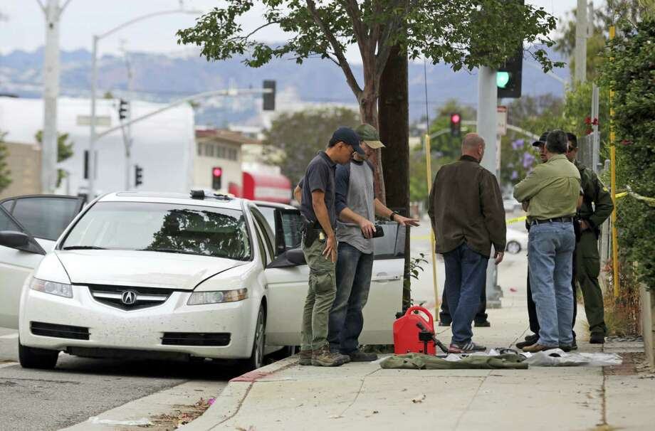 Investigators view items removed from a car, left, after a heavily armed man was arrested in Santa Monica, Calif., early Sunday, June 12, 2016. The man reportedly told police he was in the area for West Hollywood's huge gay pride parade. Authorities did not know of any connection between the gay nightclub shooting in Orlando, Fla., early Sunday and the Santa Monica arrest. Photo: AP Photo/Reed Saxon   / AP 2016