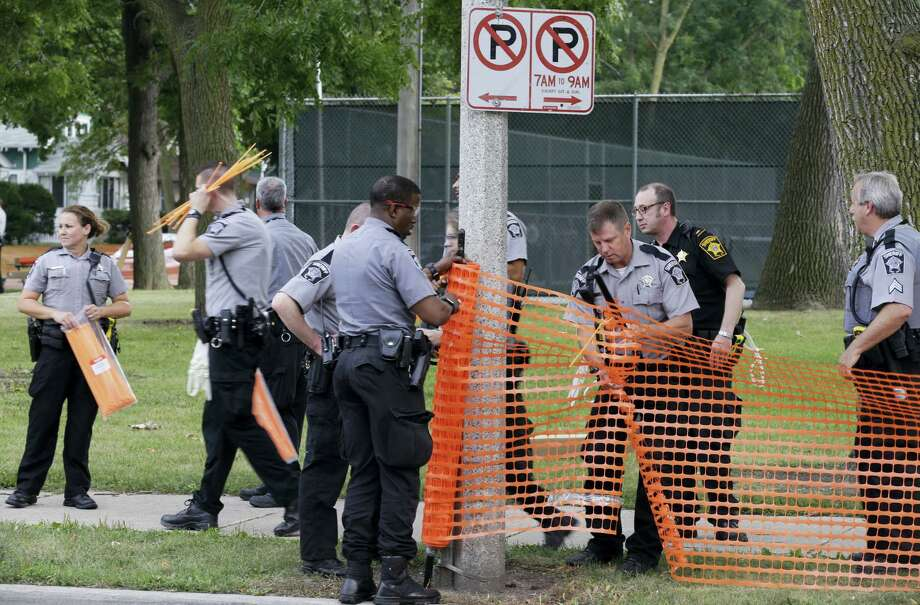Police prepare to close a park in Milwaukee Monday following a night of violence that left half a dozen businesses in flames. Photo: Jeffrey Phelps — The Associated Press  / FR59249 AP