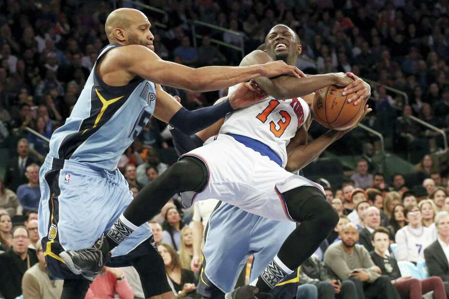 Grizzlies guard Vince Carter, left, and guard Mike Conley, in background, stop the Knicks' Jerian Grant from going to the basket during the second half on Friday. Photo: Mary Altaffer — The Associated Press  / AP
