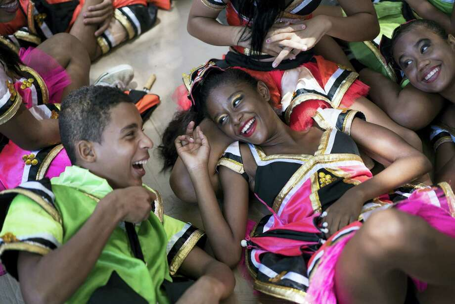 """Young revelers joke with each other as they lay on the shade during the """"Burial of the Mosquito"""" carnival block parade in Olinda, Pernambuco state, Brazil, Friday, Feb. 5, 2016. The parade that happens every year during carnival inform residents and tourists about the dangers of the Aedes aegypti and teaches them how to combat the mosquito. Photo: AP Photo/Felipe Dana   / AP"""