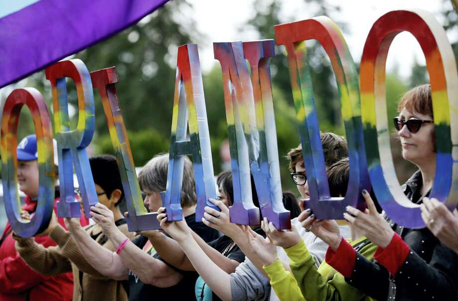 """Members of Capital City Pride and others from the LGBT community hold up letters spelling out """"Orlando"""" to honor of the recent shooting at a gay nightclub days earlier before the raising of a rainbow flag in front of the Washington state Capitol Wednesday, June 15, 2016, in Olympia, Wash. The rainbow flag was raised to mark the start of Gay Pride month, and was immediately lowered to half-staff to mark last weekend's mass shooting at a central Florida nightclub. Photo: AP Photo — Elaine Thompson / Copyright 2016 The Associated Press. All rights reserved. This material may not be published, broadcast, rewritten or redistribu"""
