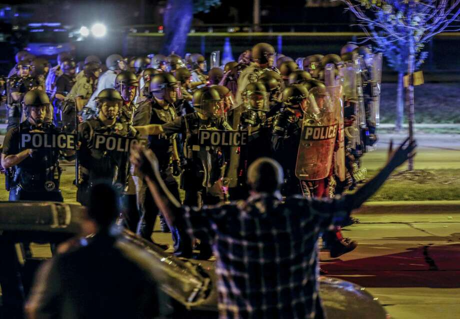 Police move in on a group of protesters throwing rocks at them in Milwaukee on Aug. 14, 2016. Police said one person was shot at a Milwaukee protest on Sunday evening and officers used an armored vehicle to retrieve the injured victim during a second night of unrest over the police shooting of a black man, but there was no repeat of widespread destruction of property. Photo: AP Photo/Jeffrey Phelps  / FR59249 AP