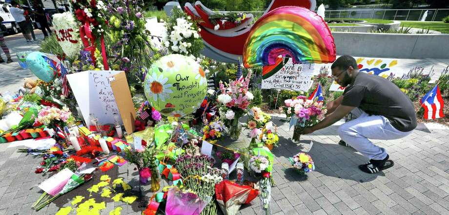 C.J. Ford of Orlando places flowers as visitors continue to pay their respects at a makeshift memorial at Orlando Regional Medical Center, a few blocks from the Pulse nightclub in Orlando, Fla.,  Tuesday, June 14, 2016. Photo: Joe Burbank — Orlando Sentinel Via AP / Orlando Sentinel