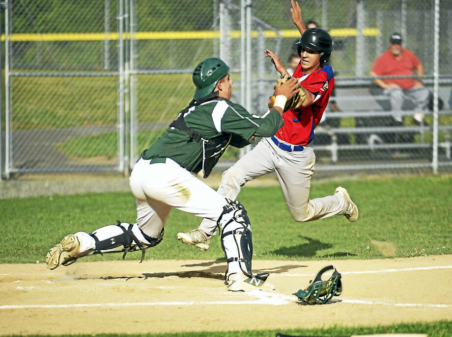 Jimmy Zanor - The Middletown Press Middletown's Jake Alonzo tries to avoid the tag from Guilford catcher Matt Donlan. Guilford prevailed Monday night in nine innings. Photo: Journal Register Co.