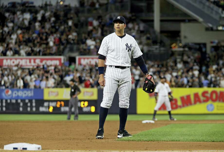 Alex Rodriguez pauses and looks into the stands after taking his position at third base during the ninth inning on Friday. Photo: Adam Hunger — The Associated Press  / FR110666 AP