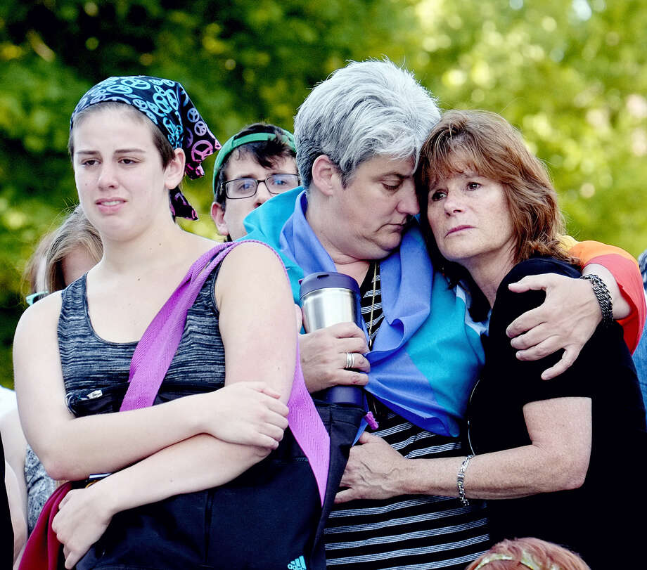 Aidan Wood, left, her mother, Lisa Laughman and Karen Pace console each other at a vigil for the mass shootings in Orlando, Fla., in Lansing, Mich. on June 12, 2016. Photo: Robert Killips/Lansing State Journal Via AP  / Lansing State Journal