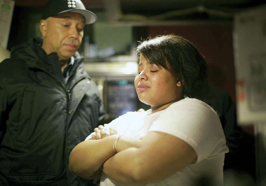 Def Jam co-founder Russell Simmons, left, listens as Nakeyja Cade, 24, a Flint resident and mother of three, speaks after he brought her family cases of water on Feb. 1, 2016 in Flint, Mich.  The Michigan Department of Environmental Quality has undertaken a five-part strategy to determine whether Flint's water, which has become contaminated with lead, is safe to drink. Photo: Regina H. Boone/Detroit Free Press Via AP  / Detroit Free Press