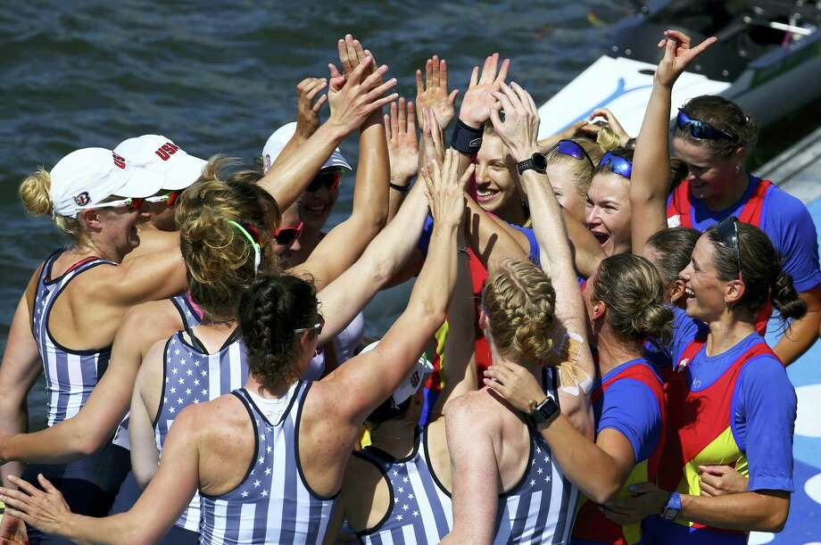 The women's rowing teams from the United States, left, and Romania celebrate on the dock after winning medals in the women's eight event at Lagoa in Rio de Janeiro, Brazil, Saturday, Aug. 13, 2016. Romania took the bronze, the United states the gold and Britain the silver. Photo: Jeremy Lee/Pool Photo Via AP   / Pool