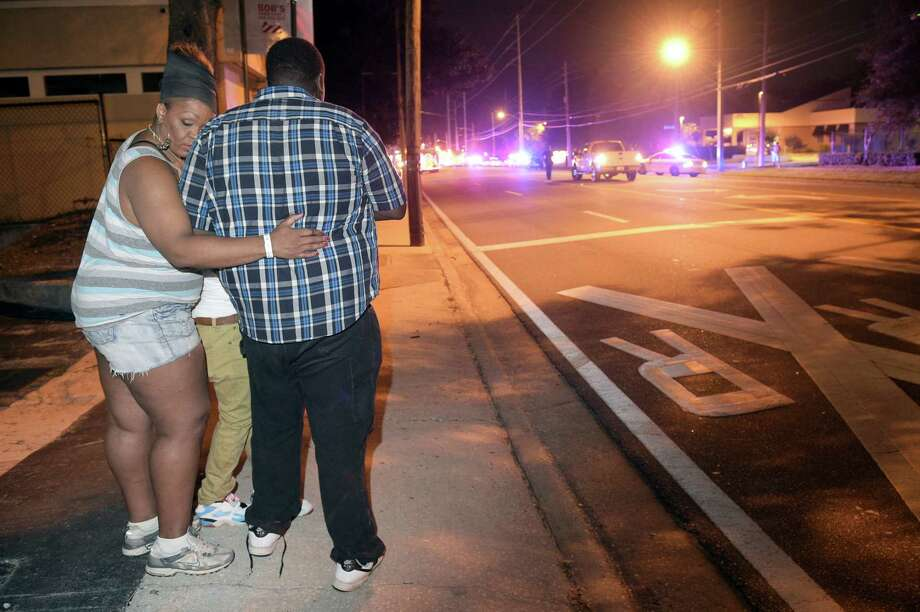 Bystanders wait down the street from a multiple shooting at the Pulse nightclub in Orlando, Fla. on June 12, 2016. A gunman opened fire at a nightclub in central Florida, and multiple people have been wounded, police said Sunday. Photo: AP Photo/Phelan M. Ebenhack  / FR121174 AP