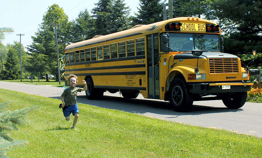 """In this 2011 photo provided by Mark Barden, his son Daniel Barden runs alongside a school bus in Newtown, Conn. Daniel was among those killed during the Sandy Hook Elementary School shootings on Dec. 14, 2012 in Newtown. Mark Barden is one of the subjects in the documentary """"Newtown,"""" which debuted earlier this year at the Sundance Film Festival. Photo: Mark Barden Via AP  / Mark Barden"""