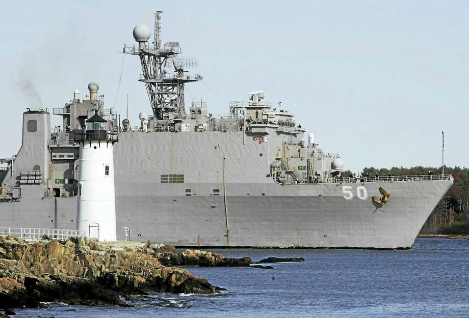 The Navy ship USS Carter Hall follows the tide out by the Portsmouth Harbor Lighthouse in New Castle, N.H. Photo: AP Photo/Jim Cole/File  / AP2009