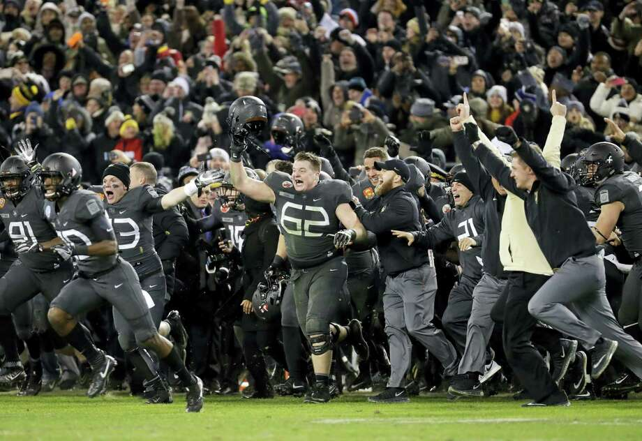 Army players and coaches run onto the field after beating Navy 21-17 in Baltimore on Saturday. Photo: Patrick Semansky — The Associated Press  / Copyright 2016 The Associated Press. All rights reserved.