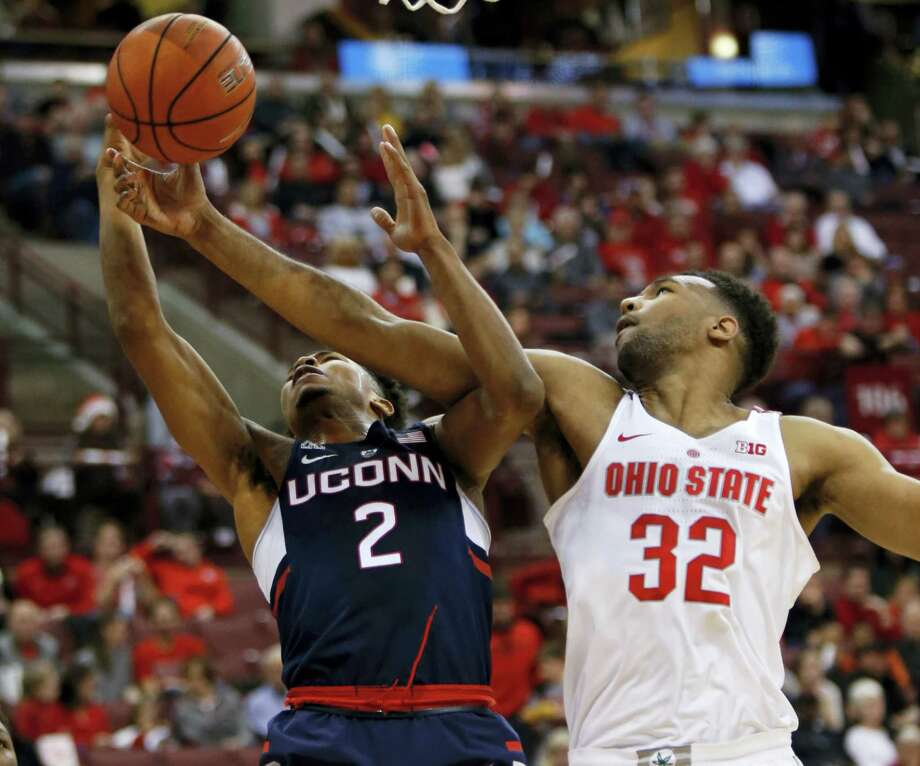 Ohio State center Trevor Thompson, right, works for a rebound against UConn's Jalen Adams during the first half Saturday. Photo: Paul Vernon — The Associated Press   / FR66830 AP
