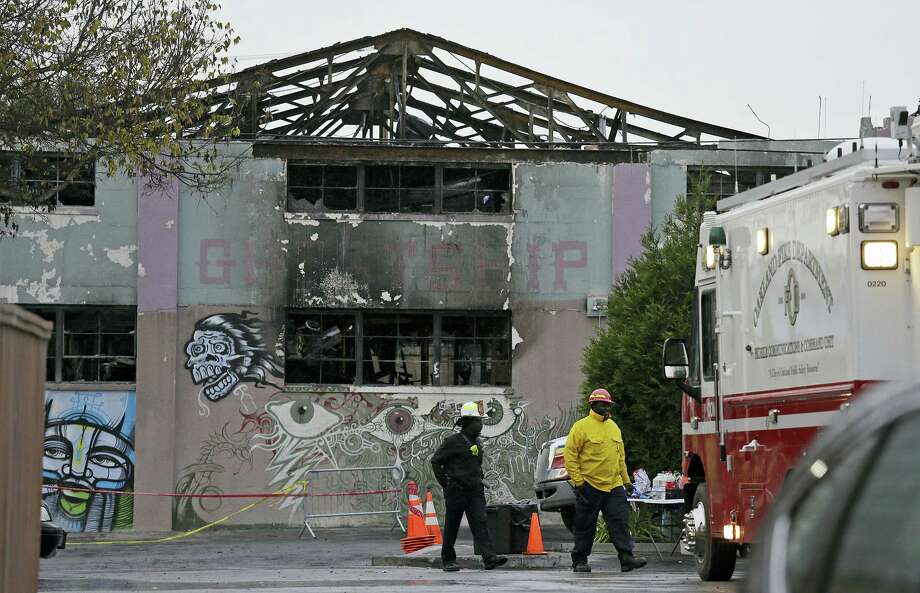 "Oakland fire officials walk past the remains of the Ghost Ship warehouse damaged from a deadly fire in Oakland, Calif. The Dec. 2 fire killed dozens of people during a electronic dance party, after it raced through the building, trapping them inside. For those who survived, it was largely a matter of luck that when the first cries of ""fire"" were heard, they were able to find their way through smoke and darkness or were near enough to a door or already outside. Photo: Eric Risberg — AP Photo  / Copyright 2016 The Associated Press. All rights reserved."