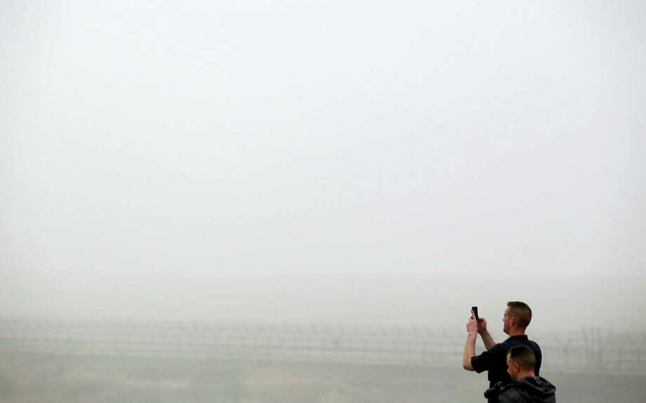 Visitors take photos on a foggy day at the Imjingak Pavilion near the border village of the Panmunjom in Paju, South Korea, Saturday, April 9, 2016. North Korea said Saturday it has successfully tested a new intercontinental ballistic rocket engine that will give it the ability to stage nuclear strikes on the United States. Photo: AP Photo/Lee Jin-man  / AP