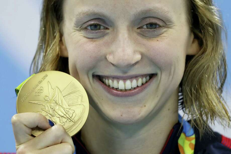 Katie Ledecky shows off her gold medal in the women's 800-meter freestyle ceremony on Friday. Photo: Michael Sohn — The Associated Press  / Copyright 2016 The Associated Press. All rights reserved. This material may not be published, broadcast, rewritten or redistribu