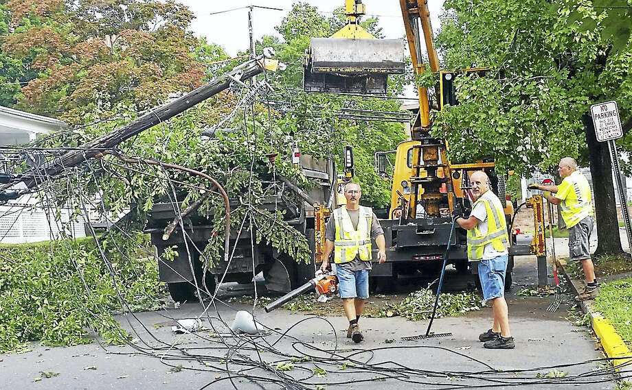 Crews worked to clean up damage on Home Avenue near Lawn Avenue in Middletown early Friday morning. Powerful storms swept through the city Thursday, bringing down a number of large trees and power lines in the roadways. Photo: Cassandra Day — The Middletown Press
