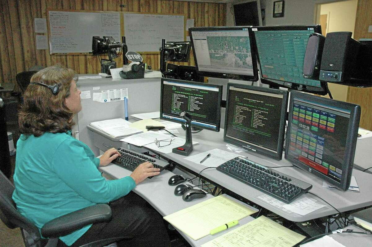 A dispatcher fields 911 calls in this archive photograph. East Hampton has until July 1 to find another dispatch center for emergency operations — it's now drafting a memorandum of understanding with Glastonbury for the service.