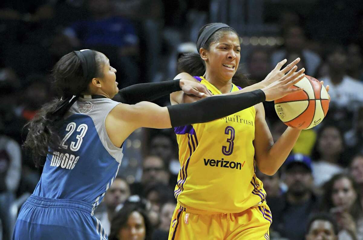Lynx forward Maya Moore, left, reaches in on Sparks forward Candace Parker during the first half on Sunday.