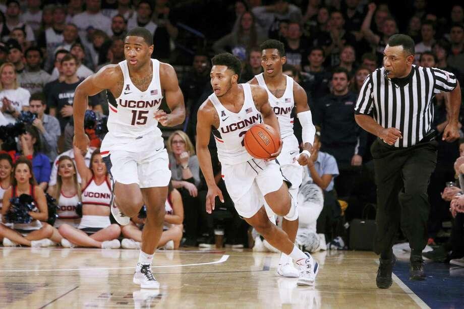 UConn's Jalen Adams (2) advances the ball with teammates Rodney Purvis (15) and Christian Vital (1) against Syracuse on Monday. Photo: The Associated Press   / FR103966 AP
