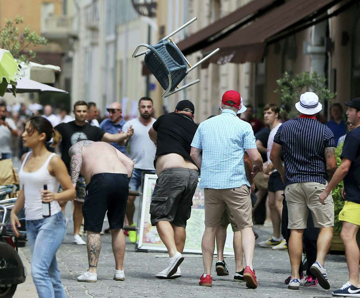 A man throws a chair as minor skirmishes continue between soccer fans in the streets of Marseille, France, ahead of the England vs Russia, Euro 2016 soccer match in France, Saturday June 11, 2016. Riot police threw tear gas canisters at soccer fans Saturday in Marseille's Old Port in a third straight day of violence in the city.