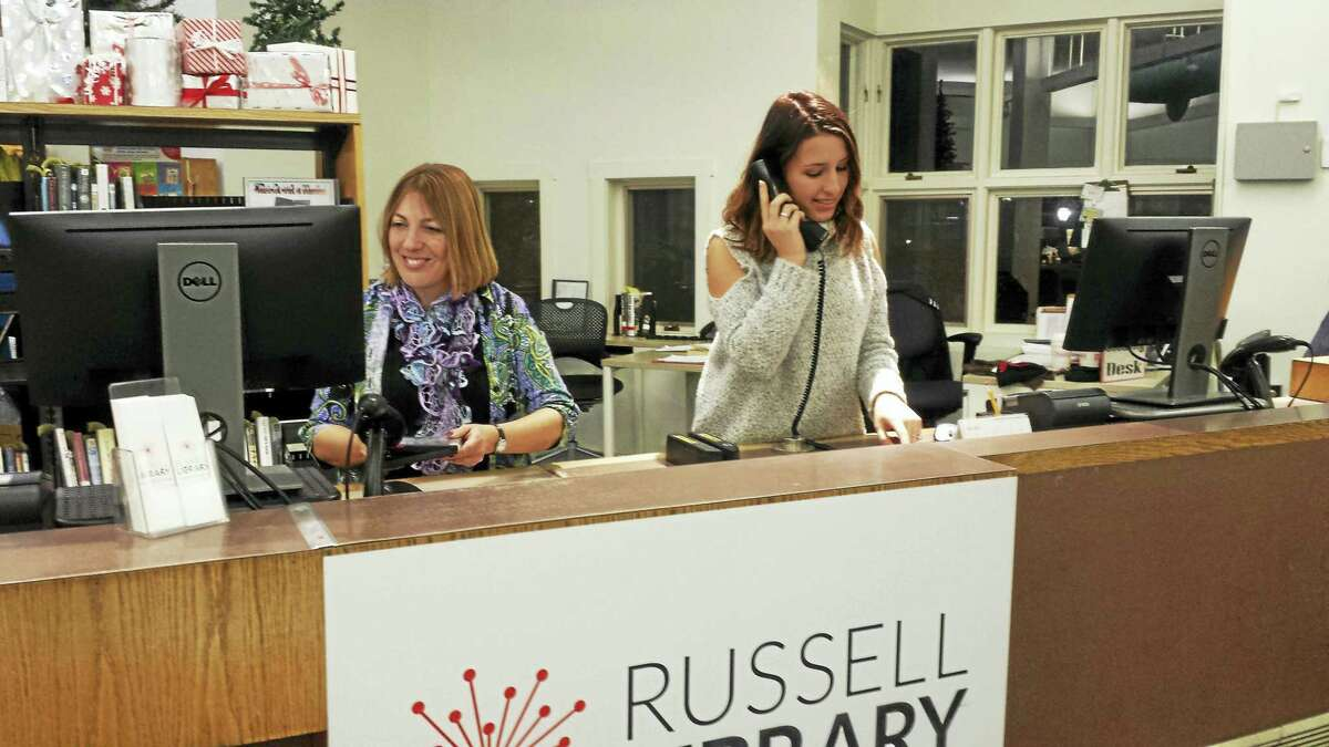 Russell Library Librarian Christy Billings, left, works at the main desk along with Charlotte Dombrowski.