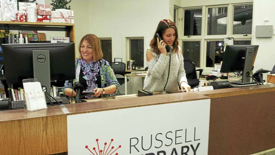 Russell Library Librarian Christy Billings, left, works at the main desk along with Charlotte Dombrowski. Photo: Cassandra Day — The Middletown Press