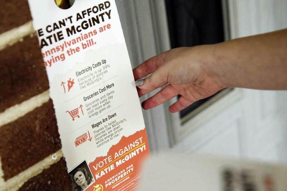 In this photo taken Oct. 13, 2016, Kathryn Ferro with Americans for Prosperity leaves information at a voters door in Bensalem, Pa. The Republican door-knockers are busy selling Pennsylvania Sen. Pat Toomey, and they never mention Donald Trump. Such is the 2016 landscape in battlegrounds across the country, where hundreds of activists tied to the billionaire Koch brothers are eschewing the top of the ticket in favor of protecting the Republican majority in the Senate. Photo: AP Photo/Matt Rourke  / Copyright 2016 The Associated Press. All rights reserved.