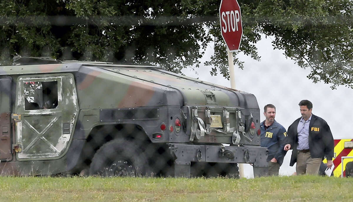 FBI officials walk behind an military vehicle near the scene of a shooting at Joint Base San Antonio-Lackland, Friday, April 8, 2016, in San Antonio.