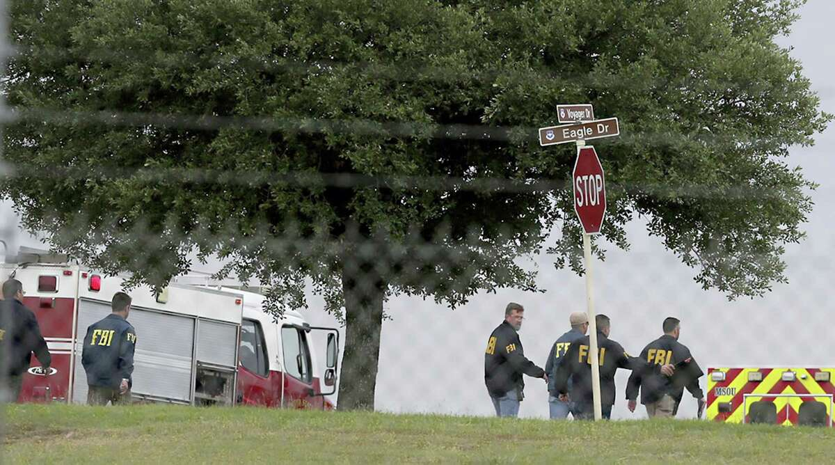 First responders and FBI agents gather near the scene of a shooting at Joint Base San Antonio-Lackland, Friday, April 8, 2016, in San Antonio.
