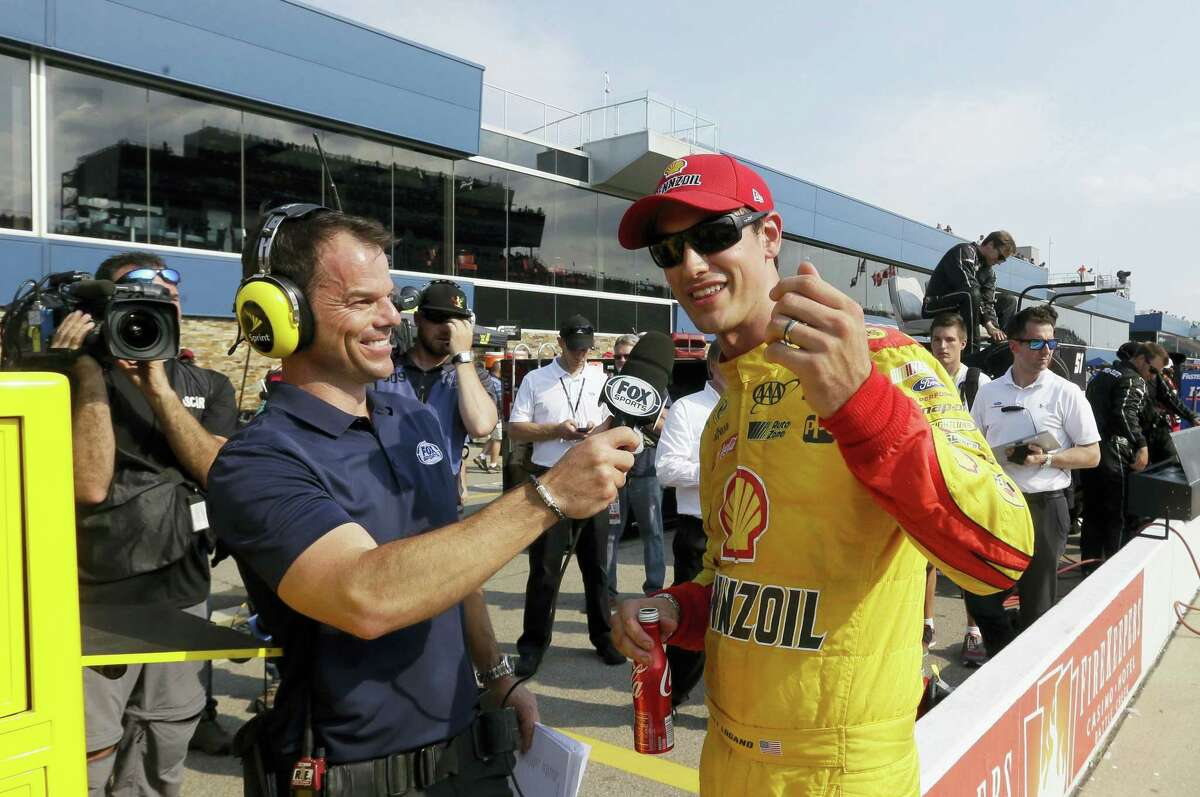 Joey Logano is interviewed after winning the pole at Michigan International Speedway on Friday.