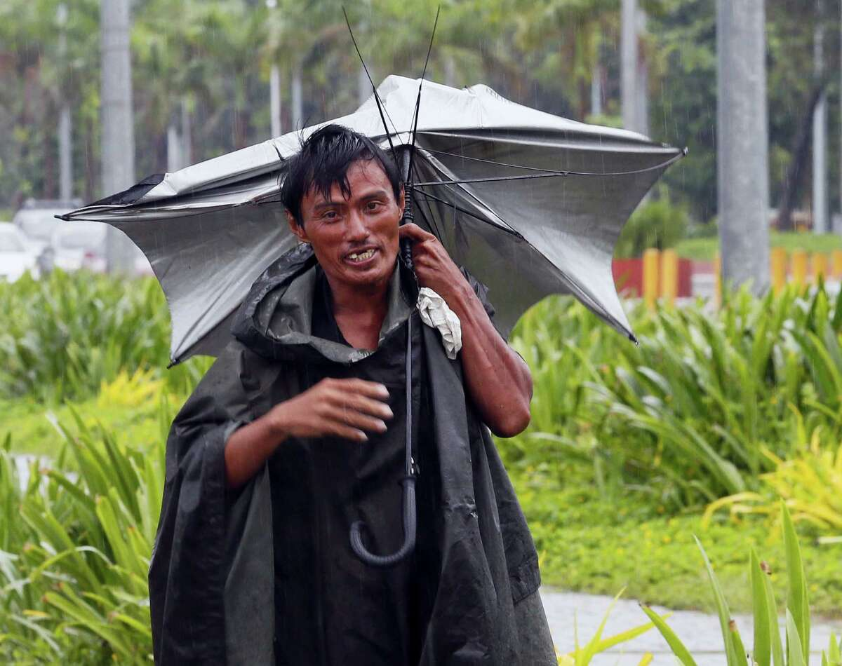 """A man walks along a boulevard with an inverted umbrella under a slight rain which was brought about by Typhoon """"Karika"""" on Oct. 16, 2016 in Manila, Philippines. The powerful typhoon, with sustained winds of 130 kilometers (80) miles per hour and gusts of 220 kph (136mph), has slammed into the northeastern Philippines and left at least two people dead, knocked out power and isolated villages in floods and toppled trees."""