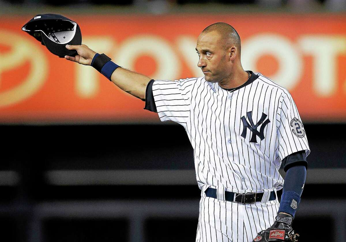 In this Sept. 25, 2014 photo, New York Yankees shortstop Derek Jeter acknowledges applause from fans as he takes the field for a baseball game against the Baltimore Orioles in New York.