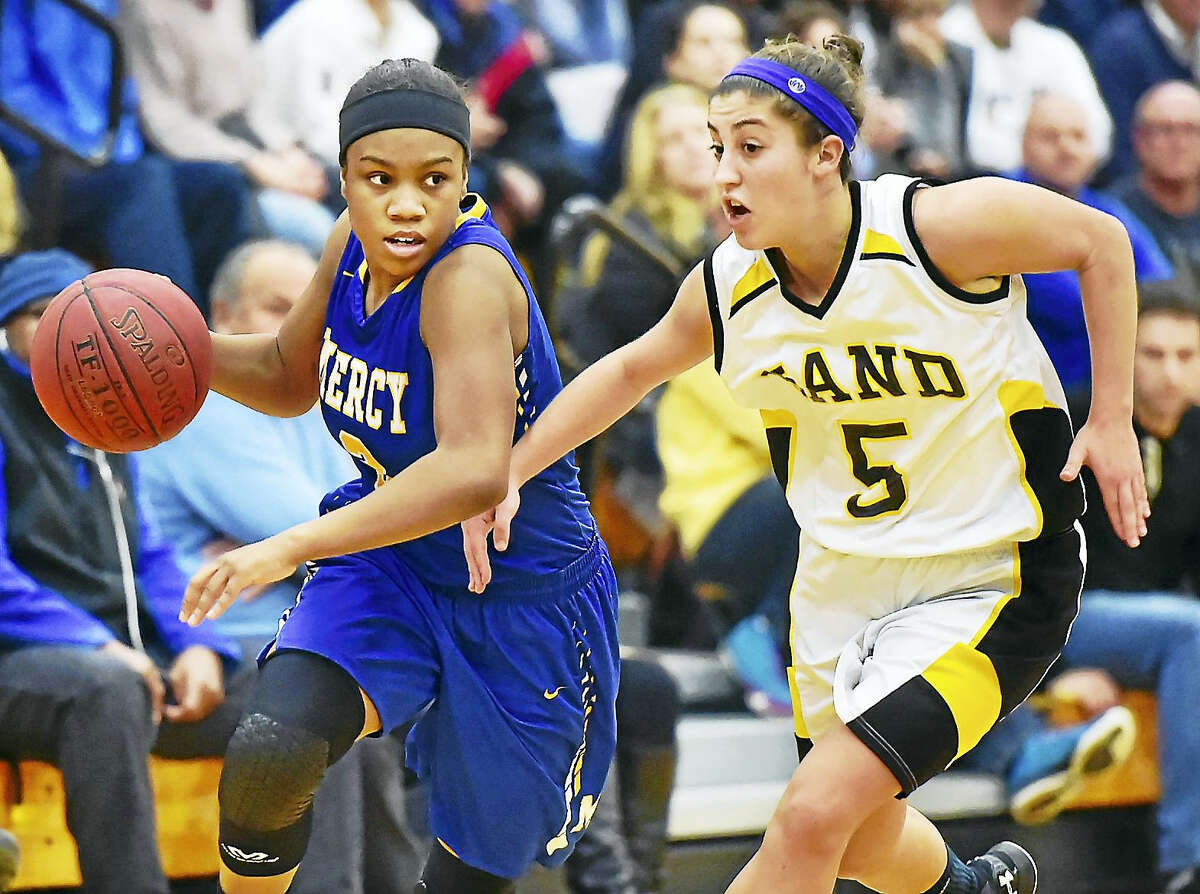 Mercy captain Destine Perry drives to the hoop as Hand's Gillian Draemer defends in a 77-56 win for the Mercy Tigers last week at Daniel Hand High School in Madison.